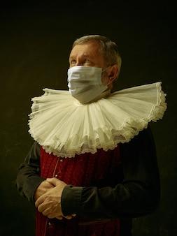 오래된 금고. 코로나바이러스에 대한 보호 마스크를 쓰고 어두운 배경에 중세 기사로 수석 남자. 복고 스타일, 시대 개념의 비교입니다. 의료, 전염병 확산 방지. 안전 유지.