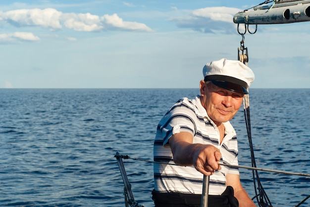 바다 경치에 대 한 그의 요트에 오래 된 선원