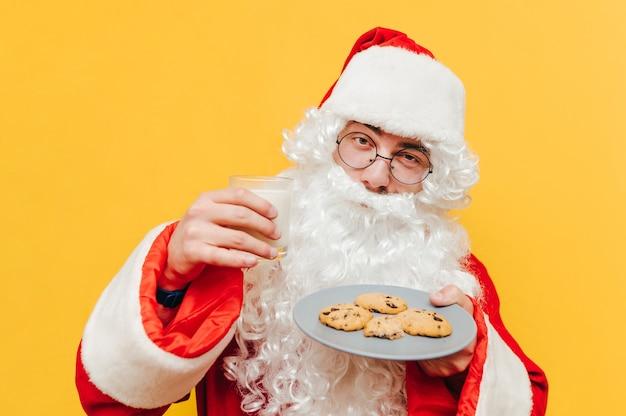 オールドサンタクロースは、牛乳とチョコレートクッキーのプレートを持っています