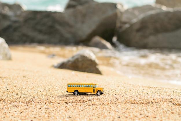 ビーチの砂の上の古い学校のバスグッズ