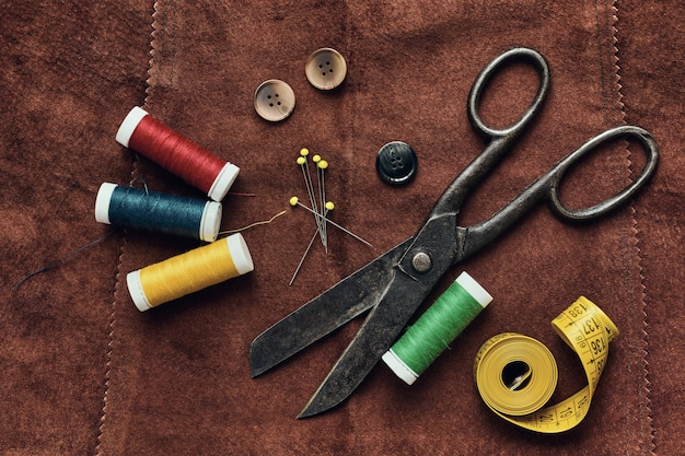 Old scissors and sewing objects on a natural suede surface
