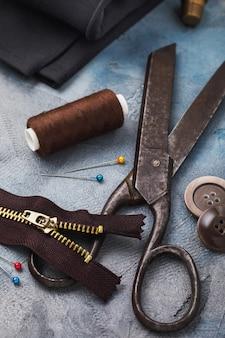 洋服用の古いはさみジッパーやその他の縫製ツールやマイナーな修理のクローズアップ