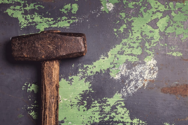 Old and scratched hammer on metal surface