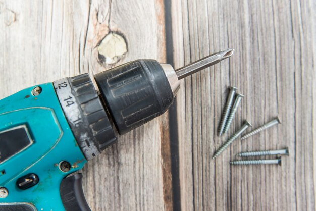 Old screwdriver and screws laying on the wooden background. flat lay view of the electric screw driver
