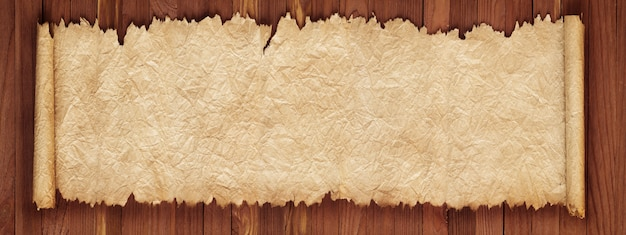 Old scroll on a wooden table, crumpled paper texture