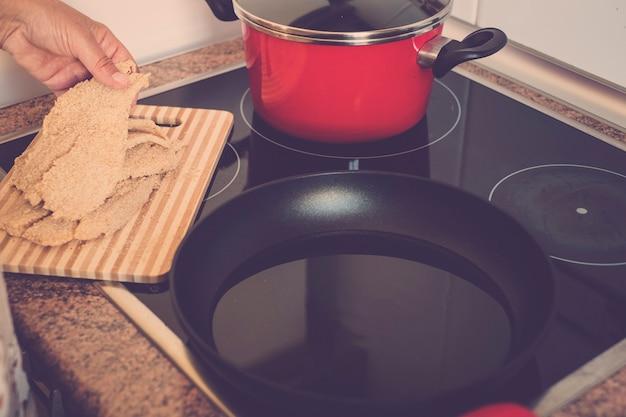 老婆と成熟した女性は、自宅のキッチンで魚や何かを調理して準備しています-一人でそしてsiolated