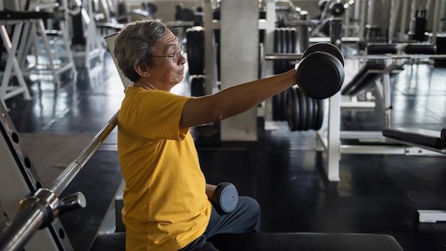 Старый старший азиатский подходящий человек поднимаясь и протягивая гантель правой рукой в тренажерном зале с задним сиденьем спортивного оборудования. упражнение на бицепс, бодибилдинг и здоровый образ жизни пожилого пенсионера.