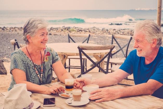 古いシニアの美しい白人カップルは、ビーチのバーでコーヒーを飲みながら、関係と生活を一緒に楽しんでいます