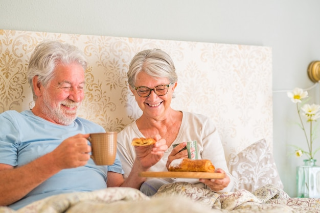 Old senior caucasian couple enjoying breakfast in the morning at bed in the bedroom at home. elderly couple eating croissant and drinking coffee from cup for breakfast at home.