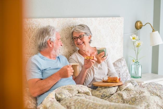 나이 든 백인 부부는 집에 있는 침실에서 아침에 웃으며 아침 식사를 즐기고 있습니다. 집에서 아침 식사로 크루아상을 먹고 컵에서 커피를 마시는 노인 부부