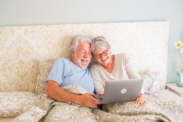 Старые старшие кавказские пары смеются и используют ноутбук утром на кровати в спальне у себя дома. пожилая пара занимается серфингом и использует социальные сети на ноутбуке дома.