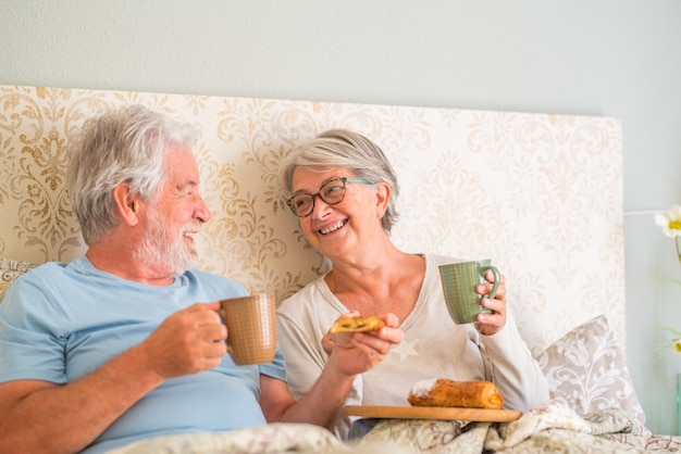 Old senior caucasian couple laughing and enjoying breakfast in the morning at bed in the bedroom at home. elderly couple eating croissant and drinking coffee from cup for breakfast at home.