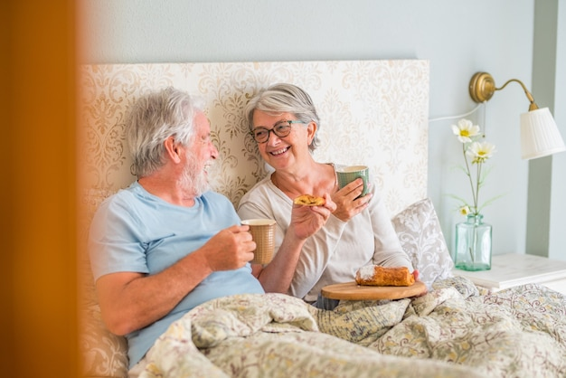 Old senior caucasian couple laughing and enjoying breakfast in the morning at bed in the bedroom at home. elderly couple eating croissant and drinking coffee from cup for breakfast at home