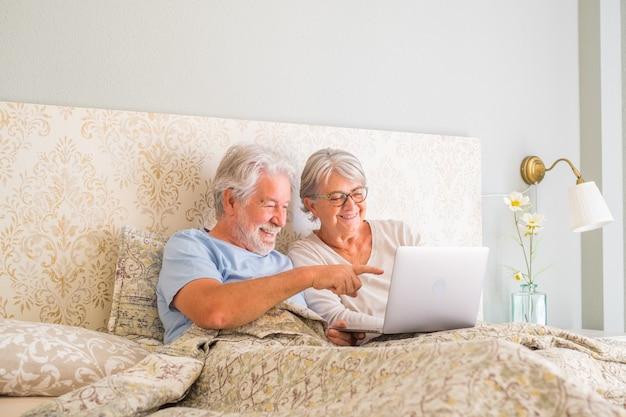 Старые старшие кавказские пары улыбаются и используют ноутбук утром на кровати в спальне у себя дома. пожилая пара занимается серфингом и использует социальные сети на ноутбуке дома. человек, указывающий на экран ноутбука