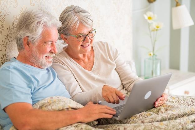 Старые старшие кавказские пары улыбаются и используют ноутбук утром на кровати в спальне у себя дома. пожилая пара занимается серфингом и использует социальные сети на ноутбуке дома.