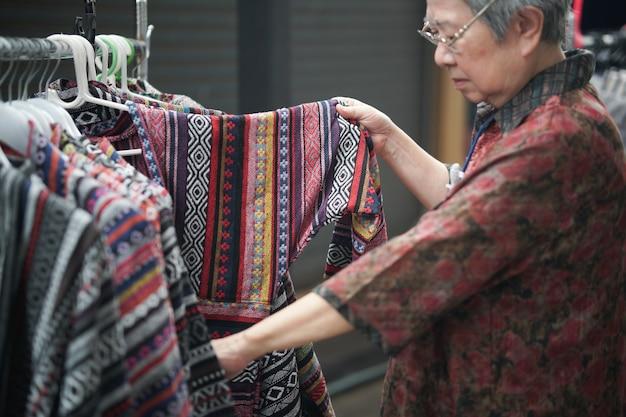 Старая старшая пожилая женщина, выбирающая одежду в торговом центре магазина