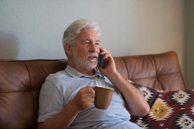 自宅で老人が現代の電話で話し、ソファに座ってコーヒーやお茶を飲み、テクノロジーのつながりを楽しんでいます-1人の成熟した男性が自宅で携帯電話を使用してリラックスして楽しんでいます