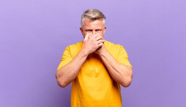 Пожилой старший мужчина прикрывает рот руками с шокированным, удивленным выражением лица, хранит секрет или говорит: ой
