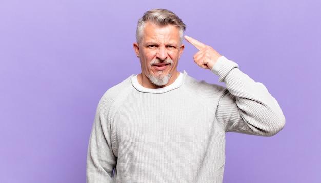 Пожилой старший мужчина смущен и озадачен, показывая, что вы сошли с ума, сошли с ума или сошли с ума
