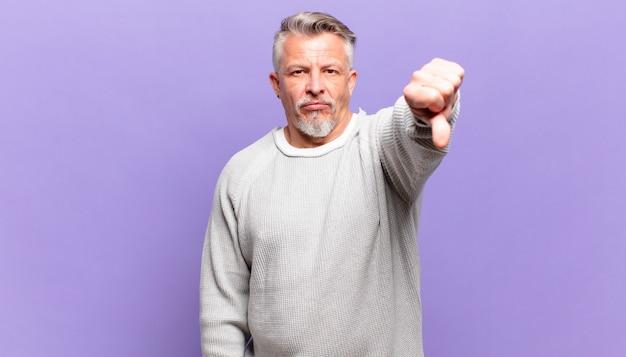 Пожилой мужчина чувствует раздражение, злость, раздражение, разочарование или недовольство, показывая большой палец вниз с серьезным взглядом