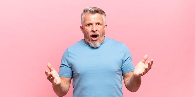 Пожилой пожилой мужчина чувствует себя чрезвычайно шокированным и удивленным, встревоженным и паническим, с напряженным и испуганным взглядом