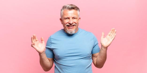 Старый старший мужчина чувствует себя счастливым, взволнованным, удивленным или шокированным, улыбается и удивляется чему-то невероятному