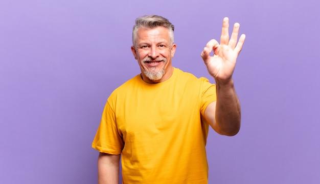 Пожилой старший мужчина чувствует себя счастливым, расслабленным и довольным, демонстрирует одобрение жестом `` ок '', улыбается