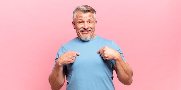 Пожилой старший мужчина чувствует себя счастливым, удивленным и гордым, указывая на себя взволнованным, изумленным взглядом