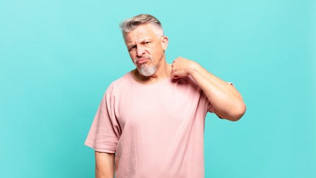 Пожилой пожилой мужчина чувствует стресс, тревогу, усталость и разочарование, дергает за шею рубашки, выглядит разочарованным из-за проблемы
