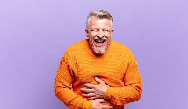 Старый старший мужчина громко смеется над какой-то веселой шуткой, чувствует себя счастливым и веселым, веселится