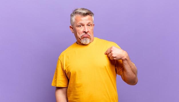 Старый старший мужчина выглядит высокомерным, успешным, позитивным и гордым, указывая на себя