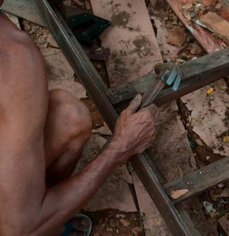 ハンマーでいくつかの木製の手作り製品を修理する老人