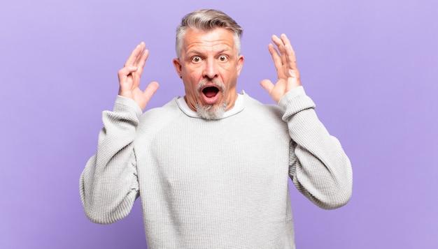 Старый старший мужчина кричит с поднятыми руками, чувствуя ярость, разочарование, стресс и расстройство