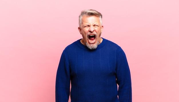 Пожилой старший мужчина агрессивно кричит, выглядит очень злым, расстроенным, возмущенным или раздраженным, кричит нет