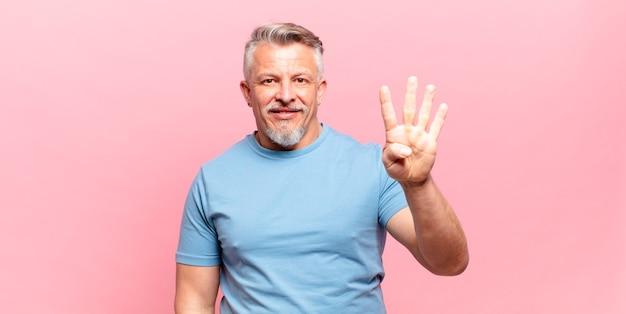 Старый старший мужчина улыбается и выглядит дружелюбно, показывает номер четыре или четвертый с рукой вперед, отсчитывая