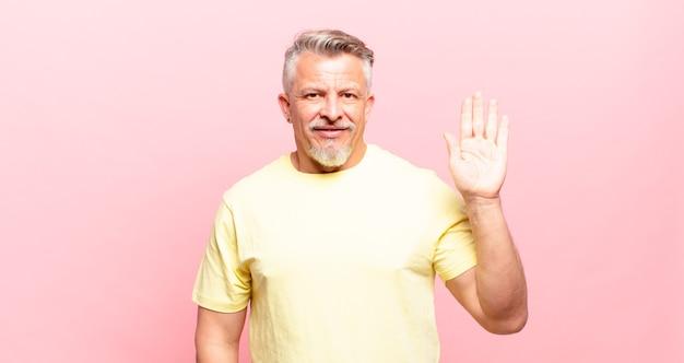 Старый старший мужчина счастливо и весело улыбается, машет рукой, приветствует и приветствует вас или прощается