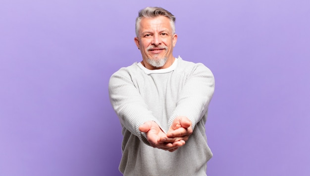 Старый старший мужчина счастливо улыбается с дружелюбным, уверенным, позитивным взглядом, предлагая и показывая объект или концепцию