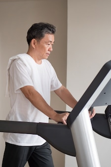 Old senior man walking, running, exercising, working out in gym with threadmill machine