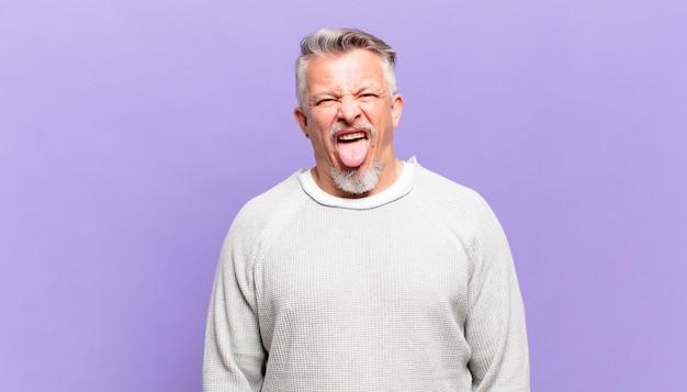 Старый старший мужчина с веселым, беззаботным, бунтарским отношением, шутит и высунул язык, весело