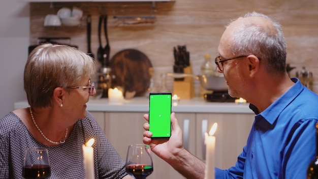 Old senior retired couple holding green screen phone at dinner. aged people looking at mockup template chroma key isolated smart phone display using techology internet sitting at the table in kitchen.
