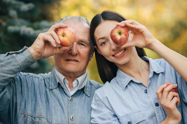 リンゴと夏の庭に立っている古いシニア