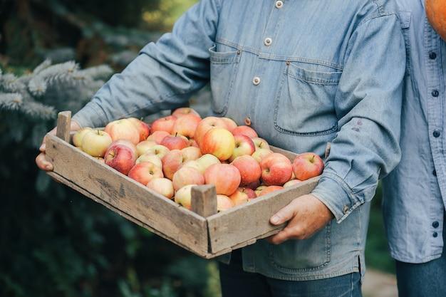 Old senior standing in a summer garden with harvest