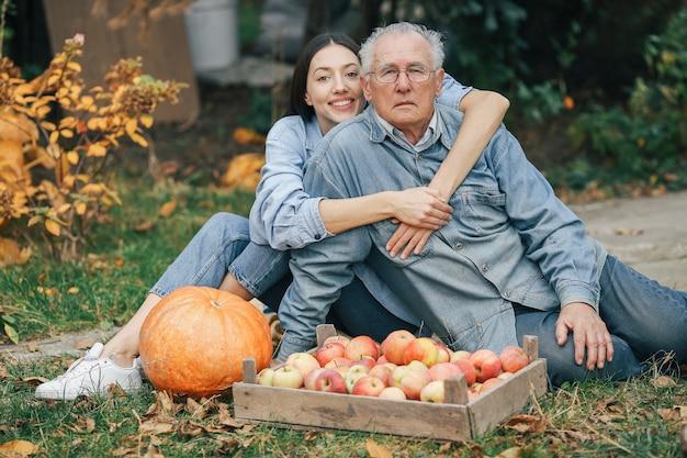 Old senior in a summer garden with granddaughter