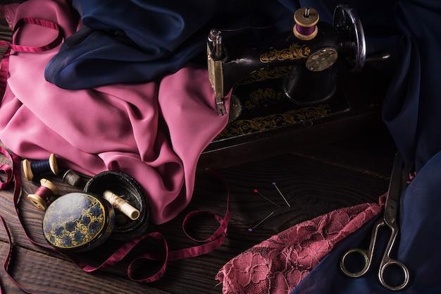 Старая швейная машина, ткани, ножницы и другие аксессуары на темном деревянном столе
