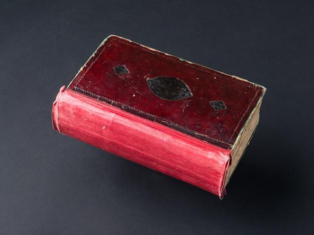 黒の背景に古いぼろぼろの本。古代の手書きの本