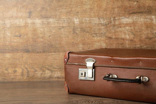 Старый потертый кожаный портативный чемодан для путешествия на коричневой стене с копией пространства