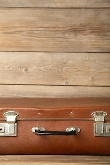 Старый потертый кожаный переносной чемодан для путешествий на сером