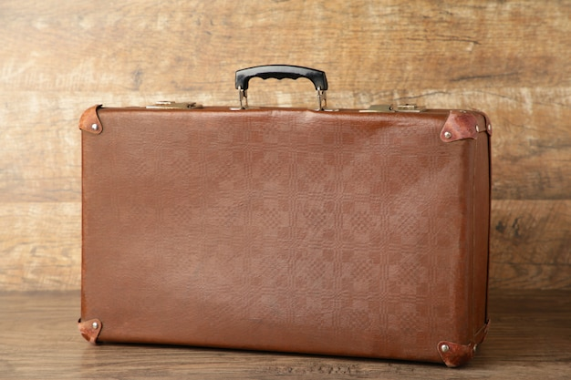 Old shabby leather portable suitcase for travel trip on brown