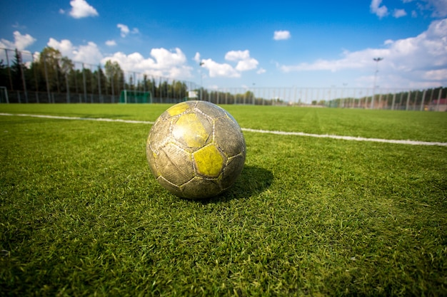 Old shabby soccer ball lying on artificial grass field