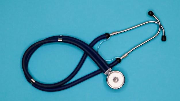Старый потрепанный стетоскоп на синем фоне.